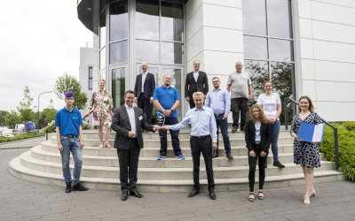 Geschäftsführer Eugen Dumitrescu erhält vor dem Firmengebäude der TRIOPTICS GmbH in Wedel von IHK-Vizepräsident Jan-Henrik Fock (Dritter von links) den Glaspokal als Auszeichnung zum TOP-Ausbildungsbetrieb. Bei der Feierstunde waren auch Mitarbeitende sowie Auszubildende des Unternehmens vertreten. (Foto: IHK/Peter Lühr)